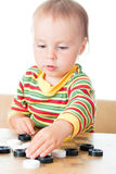 Kid playing checkers. Stock Image