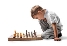 Kid playing chess. Concentrated kid playing chess into the game Royalty Free Stock Images