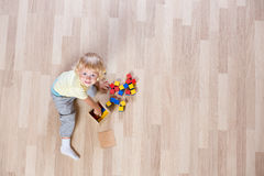 Kid playing with colorful toys on floor top view Stock Images