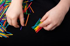 Kid playing with coloured wooden  sticks for creativity stock photo