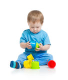 Kid playing with colourful cup toys on floor Stock Image