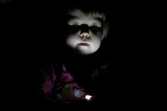 Kid playing in the dark highlighting face. Child playing in the dark highlighting face Royalty Free Stock Images