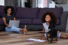 Kid playing with dog spending time with mom at home stock images