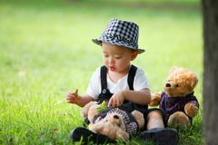 Kid playing with doll in the park Royalty Free Stock Photography
