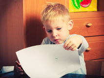 Kid playing, drawing pictures on paper Stock Photography