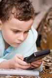 Kid playing electronic game Royalty Free Stock Image