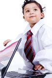 Kid playing with father's clothes and computer Stock Photography