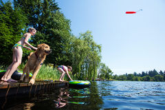 Kid playing fetch with their golden retriever dog. Two young girls playing fetch on a lake with their dog royalty free stock photography