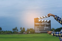 Kid playing film clapper board against summer sky background. Film director concept. Stock Photos