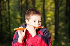 Kid playing flute in dark forest Royalty Free Stock Photography