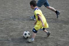 Kid playing football. Kid is kicking a ball while grown man is playing defense Royalty Free Stock Photo