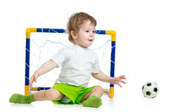 Kid playing football and catching soccer ball Royalty Free Stock Image