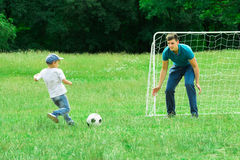 Kid Playing Football With His Father. Father And Son Playing Soccer On A Green Grass In The Park Stock Photo
