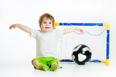 Kid playing football and sitting in front of the gate Royalty Free Stock Images
