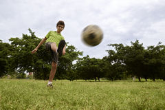 Kid playing football and soccer game in park Royalty Free Stock Images
