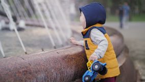 The kid is playing at the fountain. Children`s joy, happy childhood. Family values.  stock footage