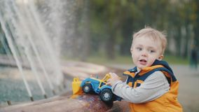Boy plays at the fountain in the park. Children`s joy, happy childhood. Family values. The kid is playing at the fountain. Children`s joy, happy childhood stock video