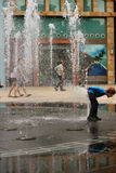 Kid playing with the fountain in Singapore. A small child playing on the fountain in Singapore, Sentosa royalty free stock photography