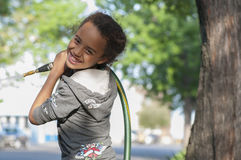 Kid playing with garden hose. Stock Photos