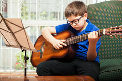Kid playing guitar at home Stock Images