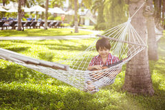 Young mixed Asian boy Kid playing guitar on a hammock outdoor Stock Photo