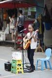 Kid playing guitar, singing Stock Image