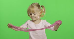 Kid playing with hand made toy slime. Child having fun making pink slime stock video footage