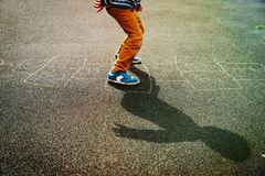Kid playing hopscotch on playground. Kids outdoor activities Stock Image