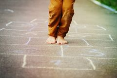 Kid playing hopscotch on playground Stock Image