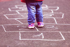 Kid playing hopscotch on playground outdoors Royalty Free Stock Image