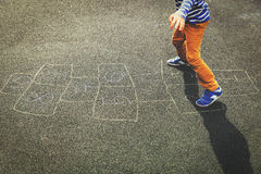 Kid playing hopscotch on playground Royalty Free Stock Photography
