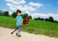 Kid playing with horse stick. Pretending to be a cowboy Royalty Free Stock Photo