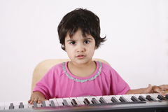 Kid playing a keyboard Stock Images