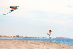 Kid playing with kite near the seaside Stock Image
