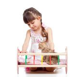 Kid playing with a kitten and rocking him in doll Royalty Free Stock Photography