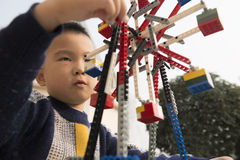 Kid playing lego block. Asian kid playing lego block toy ferris wheel outdoor Stock Photography