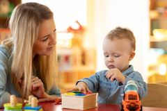 Kid playing logical toys with educator or mother in the classroom in nursery or preschool. Baby playing logical toys with educator or mother in the classroom in royalty free stock photo