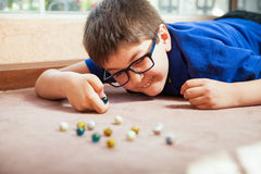 Kid playing with marbles. Young white boy playing with marbles and aiming at one at home Stock Photography