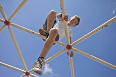 Kid playing on monkey bars Royalty Free Stock Image