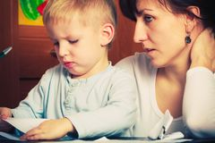 Kid playing with mother, drawing pictures on paper Royalty Free Stock Image