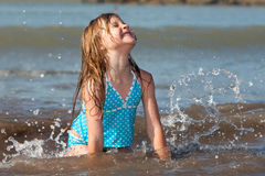 Kid playing in the ocean. Little girl playing in the ocean waves Royalty Free Stock Photo