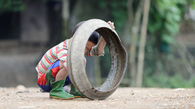 Kid playing with old tire in Sa Pa Valley stock images