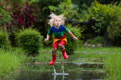 Free Kid Playing Out In The Rain. Children With Umbrella And Rain Boots Play Outdoors In Heavy Rain. Little Boy Jumping In Muddy Puddle Stock Images - 131733934