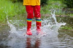 Kid playing out in the rain. Children with umbrella and rain boots play outdoors in heavy rain. Little boy jumping in muddy puddle