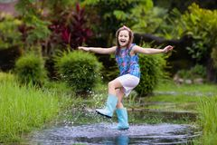 Kid playing out in the rain. Children with umbrella and rain boots play outdoors in heavy rain. Little boy jumping in muddy puddle. Kids fun by rainy autumn royalty free stock images