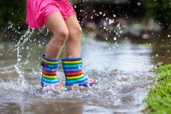 Kid playing out in the rain. Children with umbrella and rain boots play outdoors in heavy rain. Little girl jumping in muddy. Puddle. Kids fun by rainy autumn stock photography