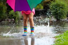 Kid playing out in the rain. Children with umbrella and rain boots play outdoors in heavy rain. Little girl jumping in muddy. Puddle. Kids fun by rainy autumn royalty free stock images