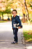 Kid playing outdoors with skateboard Stock Photos