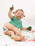 Kid playing with paint. Happy child plays in the paint at home during the renovation Stock Photography