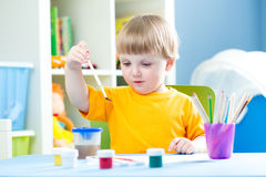 Kid playing and painting at home or kindergarten or playschool Royalty Free Stock Image